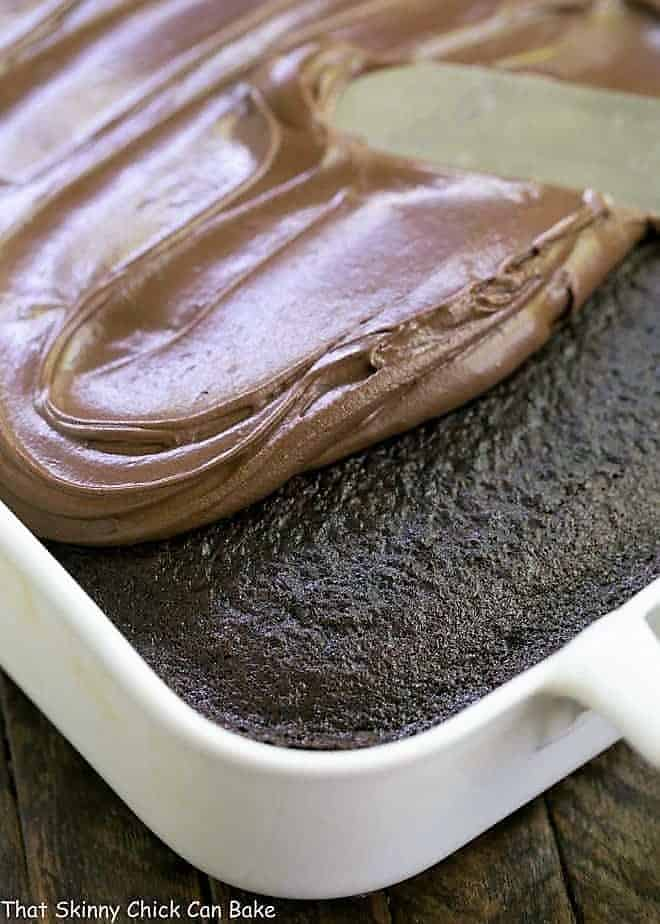 Black Magic Snack Cake in a white 9 x 13-inch pan partially frosted with chocolate buttercream