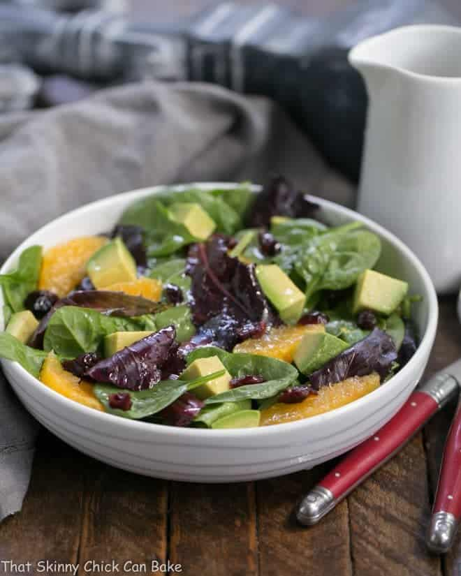 A tasty Citrus Spinach Salad with Avocados and Oranges in a white bowl drizzled with vinaigrette