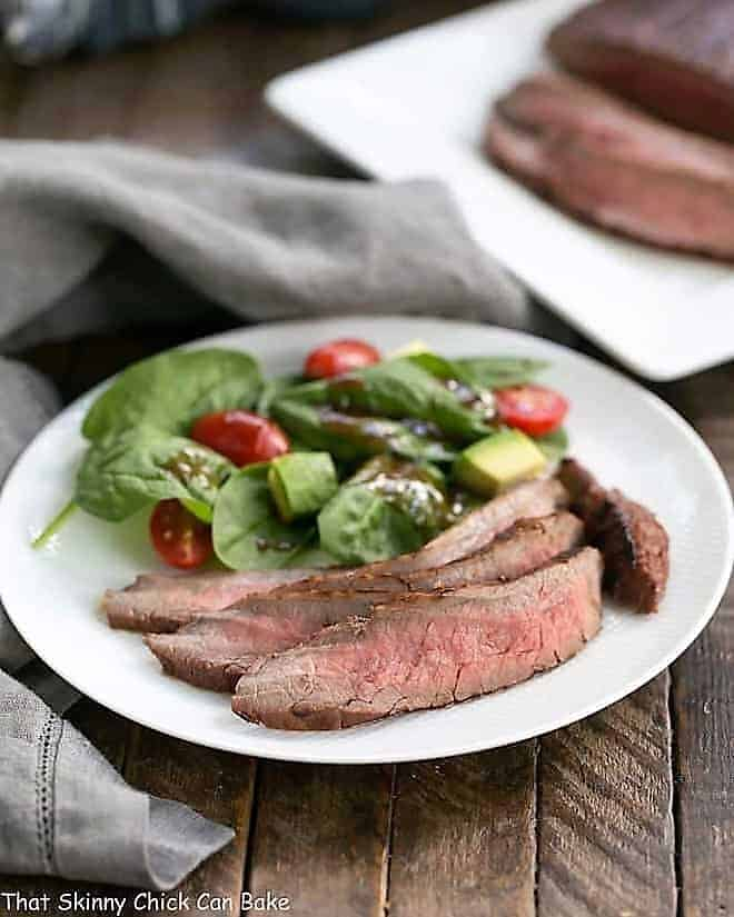 Red Wine, Soy, Balsamic Marinated Flank Steak on a white dinner plate
