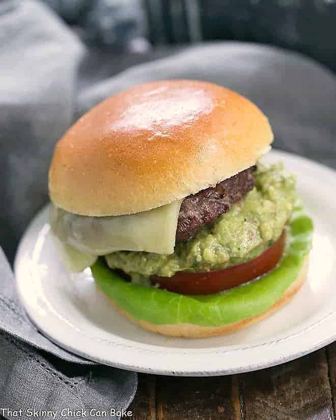 Grilled Guacamole Burger on a round white plate topped with cheese, guacamole, tomato and lettuce