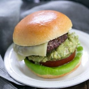 Grilled Guacamole Burger - a grilled beef hamburger topped with melted Monterey jack cheese and a creamy mound of guacamole