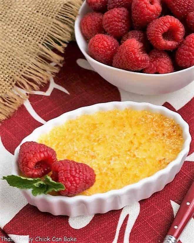 Classic Crème Brûlée in a white ramekin with a raspberry garnish