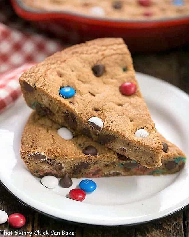Patriotic Skillet Cookie wedges stacked on a white enamel dessert plate