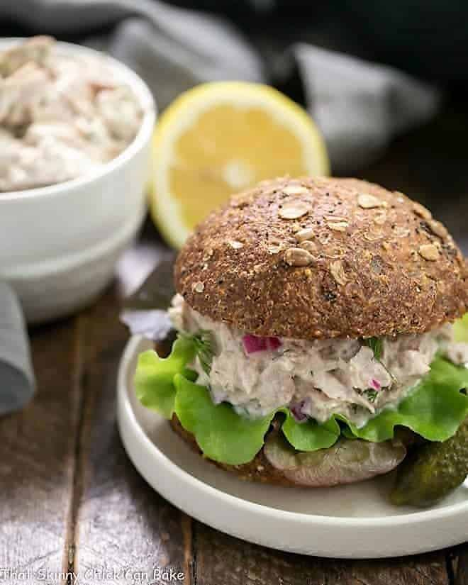 Easy Tuna Salad with Fresh Dill on a whole wheat bun on a white plate