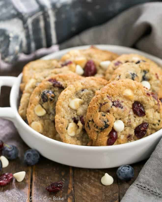 White Chocolate Chip Cookies with Dried Berries in a white ceramic terrine.