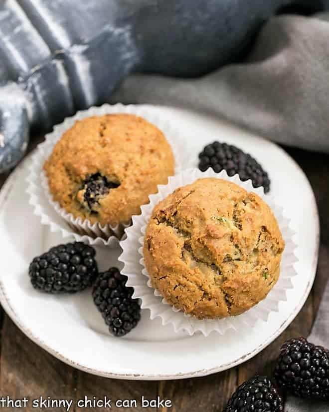 Blackberry Bran Muffins on a white plate garnished with berries
