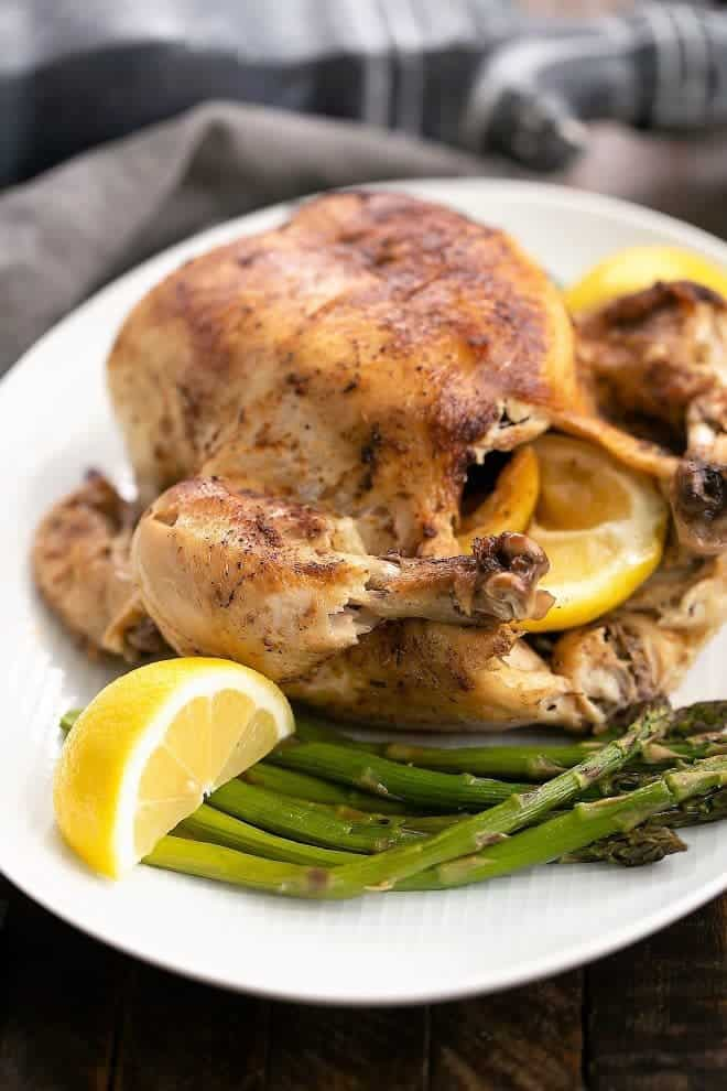 Whole Instant Pot Rotisserie Chicken on a white platter with lemon wedges
