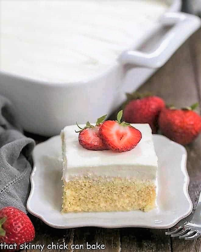 Authentic Tres Leches Cake slice on a square plate with full cake in the background