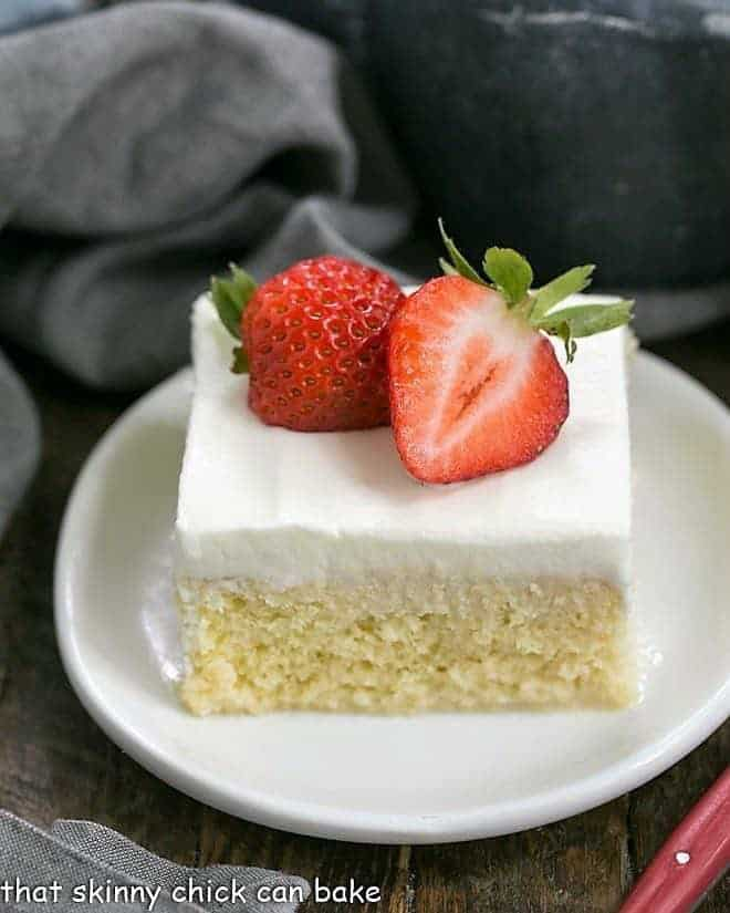 A slice of Authentic Tres Leches Cake on a white cake topped with strawberries