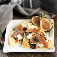 Fig, Goat Cheese and Prosciutto Pizza slices on a square white plate