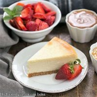 Perfect vanilla cheesecake with bowls of strawberries and toppings