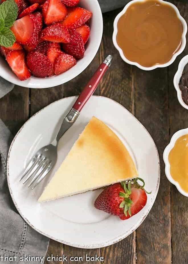 Overhead of perfect vanilla cheesecake with a bowl of strawberries and toppings