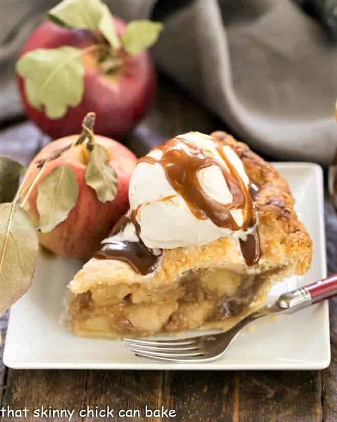 Caramel Apple Pie on a square white plate topped with ice cream and caramel sauce