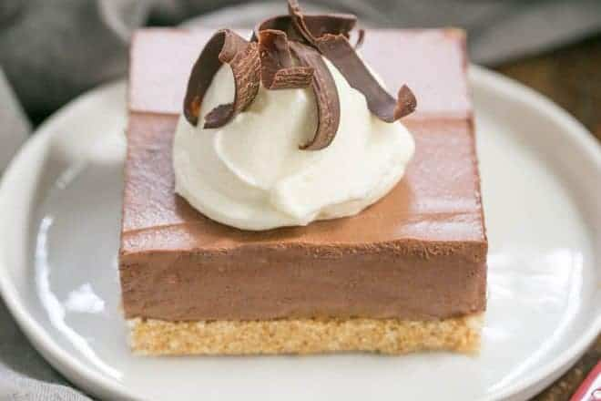 Easy chocolate mousse bars on a white plate with cream and chocolate shavings
