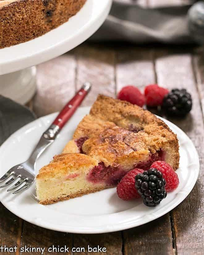 Mixed Berry Torte on a white plate with berries and a red handled fork