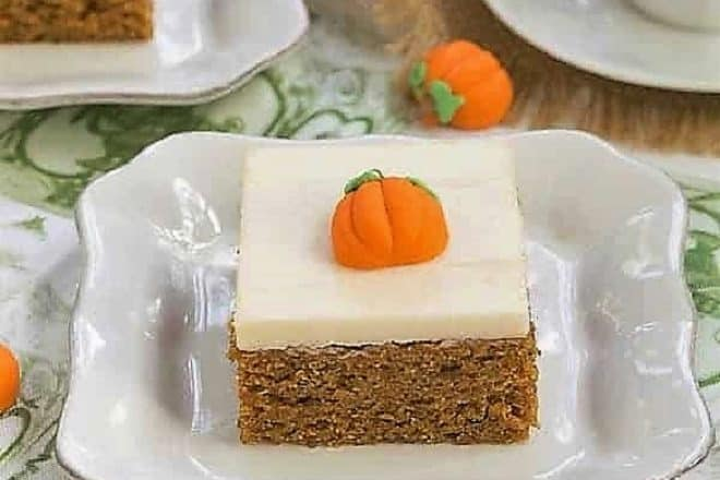 Killer Pumpkin Bars with Cream Cheese Frosting on a white ceramic plate with a candy pumpkin garnish