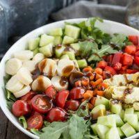 Easy Balsamic Vinaigrette on a vegetable salad in a white bowl