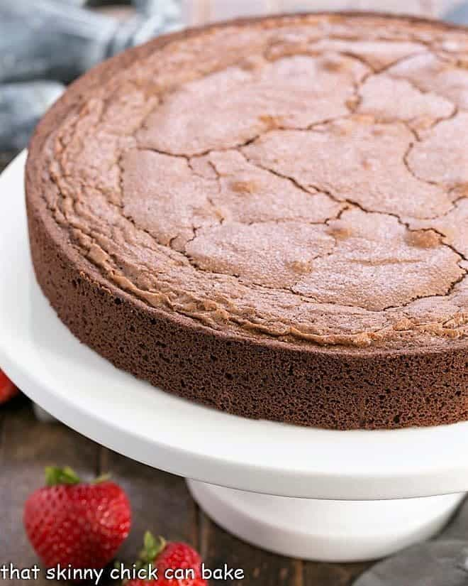 Italian Flourless Chocolate Cake on a white ceramic cake stand
