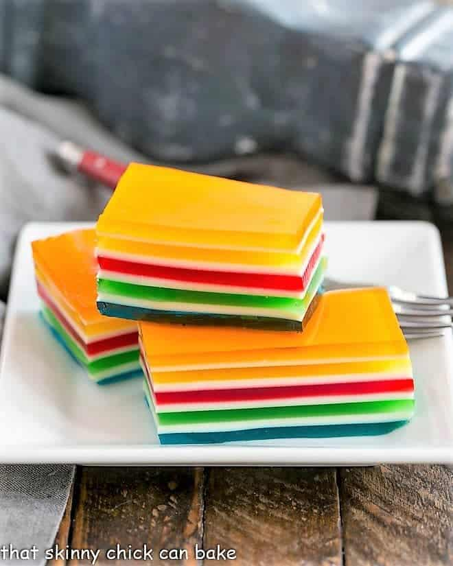 Layered Jello Rainbow Salad squares stacked on a white plate