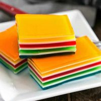 Jello Rainbow Ribbon Salad slices on a square white plate