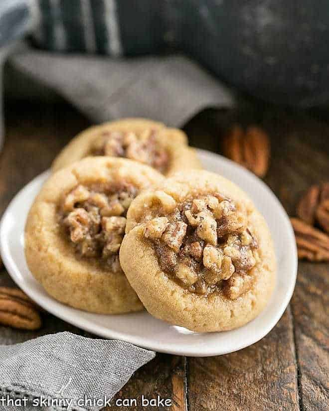 3 pecan pie thumbprint cookies on an oval plate