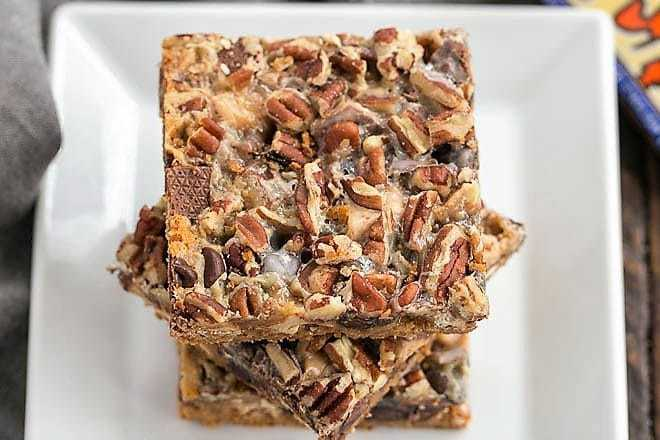 Toffee Caramel Magic Cookie Bars stacked on a white plate