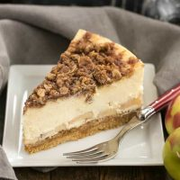 Slice of apple crisp cheesecake on a square white plate