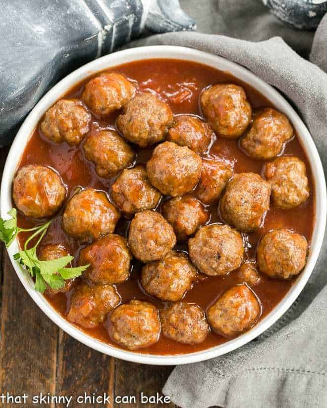 Overhead view of apricot glazed cocktail meatballs in a white serving bowl