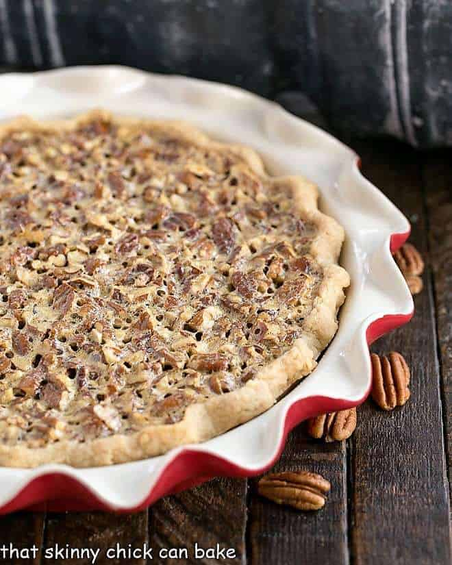 Classic Pecan Pie in a red pie plate with pecan halves