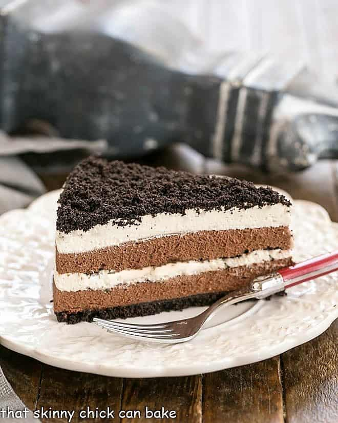 Slice of Layered Chocolate Cream Torte with a red handled fork on a white plate