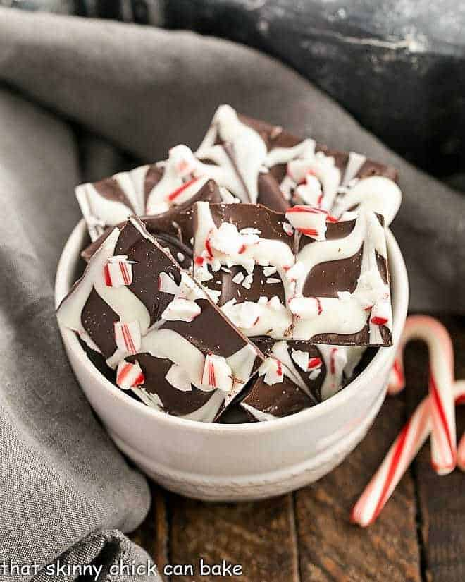 Swirled Peppermint Bark in a white bowl with candy canes