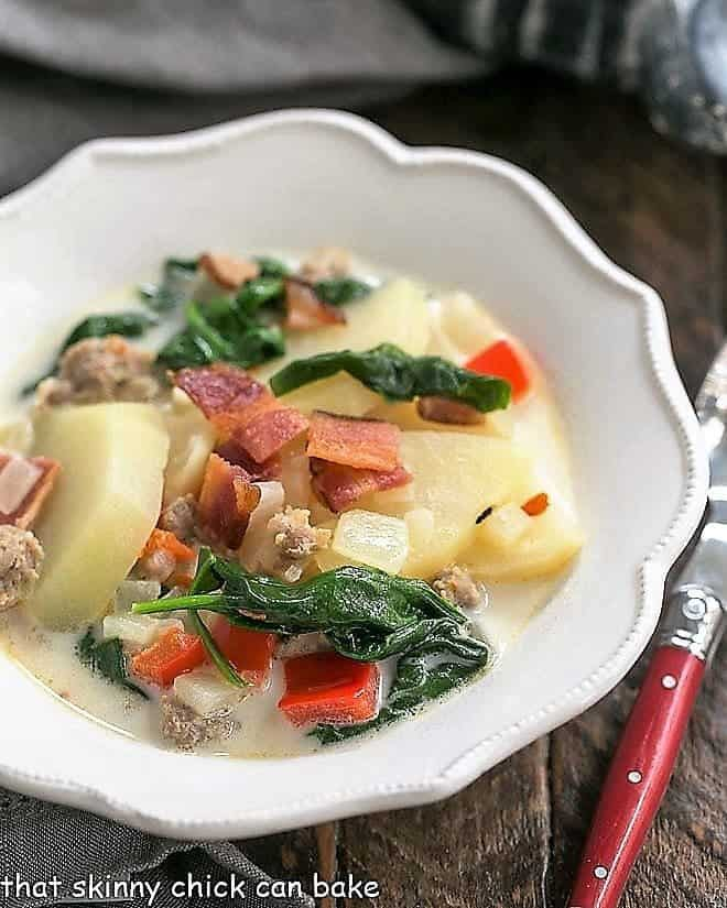 Zuppa Toscana or Tuscan Sausage Soup in a white, ruffle edged soup bowl