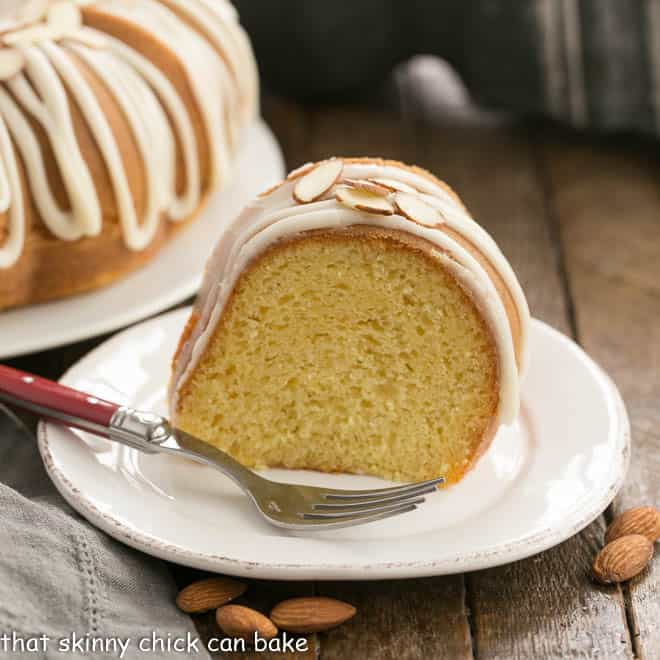 Slice of Easy Almond Bundt Cake with Amaretto Glaze on a white dessert plate