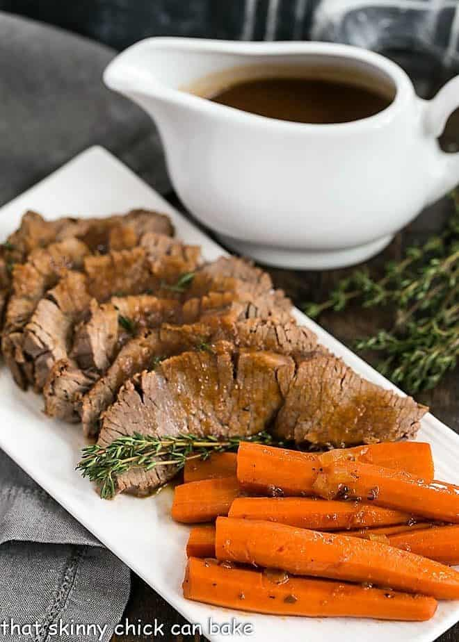 Braised Cola Brisket with Bourbon Gravy on a white platter with carrots and a pitcher of gravy