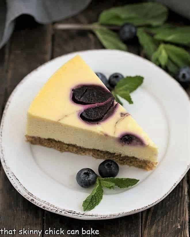 Blueberry Swirl Cheesecake slice on a white plate with mint and fresh blueberries