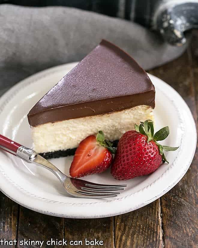 Ganache Topped Cheesecake slice on a white plate with strawberries