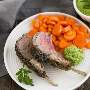 Herb Crusted Rack of Lamb with carrots and parsley pesto on a white dinner plate