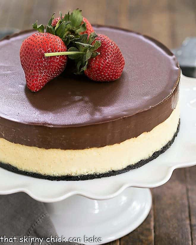 Ganache Topped Cheesecake on a white cake stand topped with large strawberries
