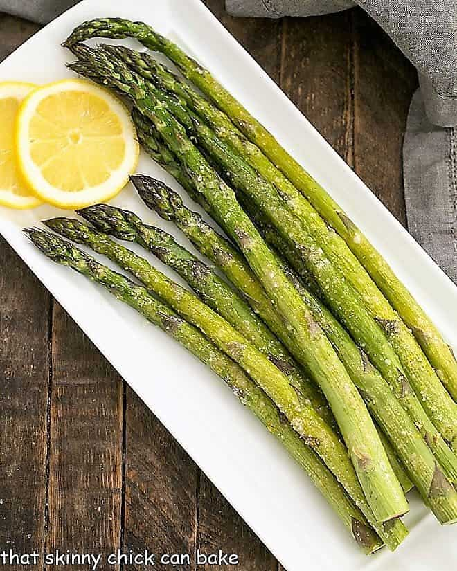 Overhead view of Easy Oven Roasted Asparagus on a white tray with lemon slices