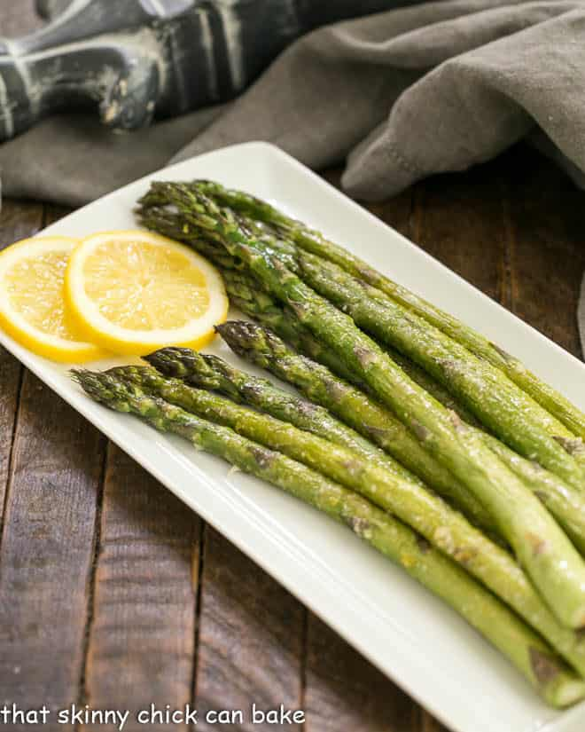 Easy Oven Roasted Asparagus on a white tray with lemon slices to garnish