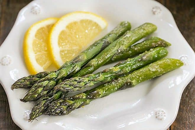 Overhead view of Easy Oven Roasted Asparagus on a white plate with lemon slices
