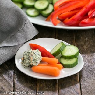 Sour Cream Spinach Dip on a small white plate with crudite
