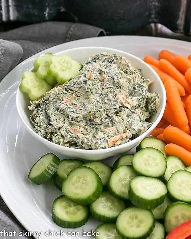 Bowl of Sour Cream Spinach Dip on a white crudite platter
