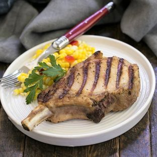 Grilled marinated pork chop on a dinner plate with fresh corn and a red handled fork