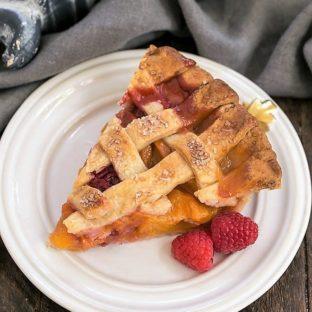 Overhead view of Peach raspberry pie slice on a white dessert plate