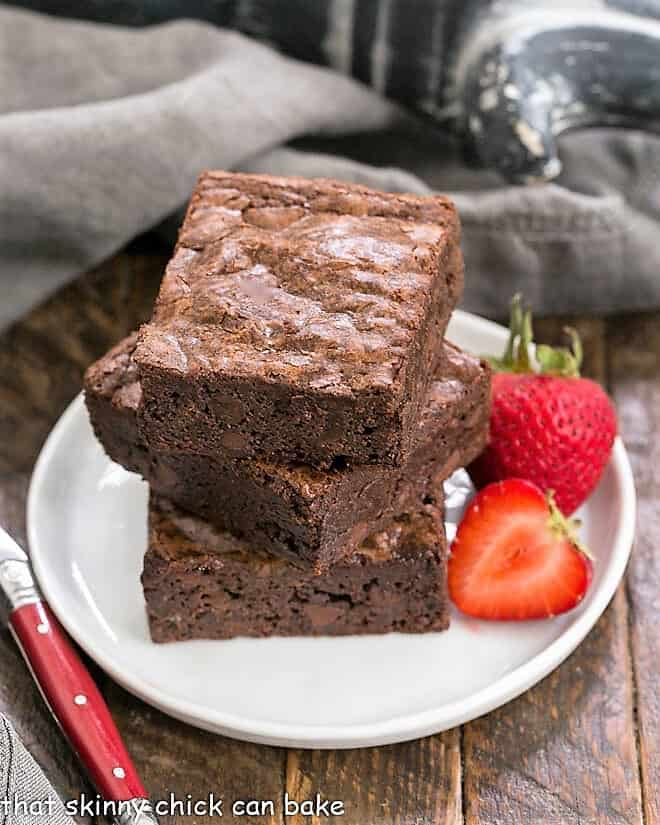 A stack of 3 homemade sheet pan brownies on a small white plate