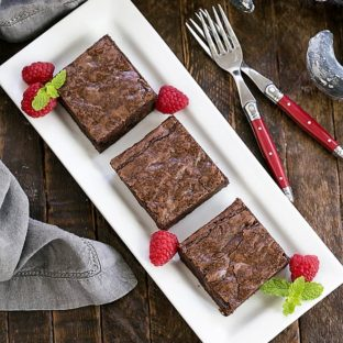 3 sheet pan brownies on a white tray with raspberries and mint