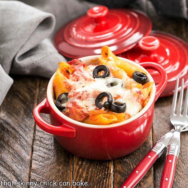 Cheesy Pasta Bake in a red crock with two forks