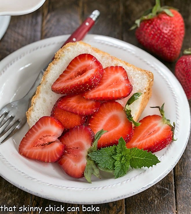 Slice of angel food cake on a white plate topped with berries