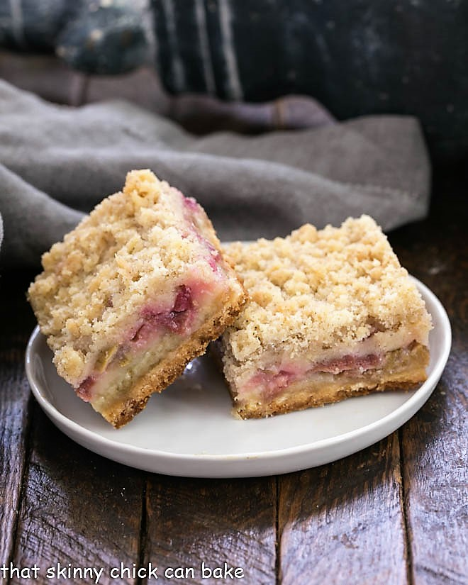 Side view of Two Streusel Topped Rhubarb Bars on a round white plate